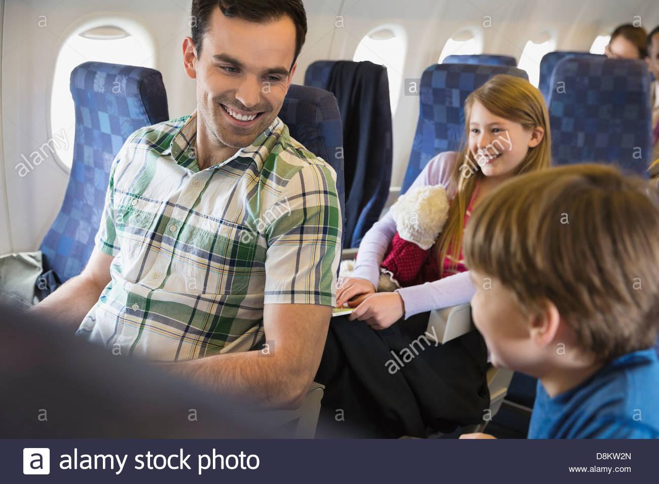 Père avec les enfants qui voyagent en avion Photo Stock