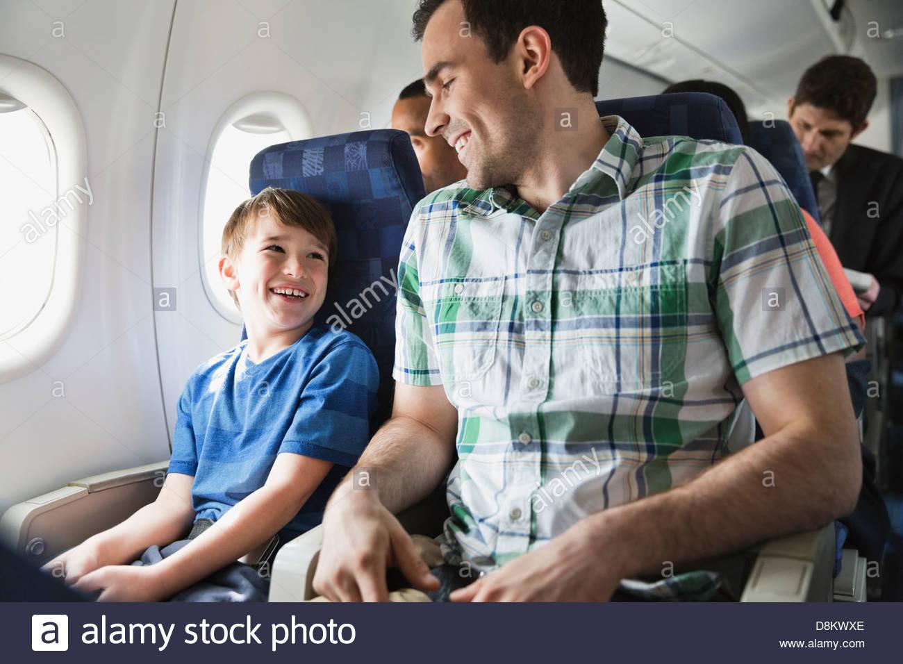 Smiling père et fils voyageant en avion Photo Stock