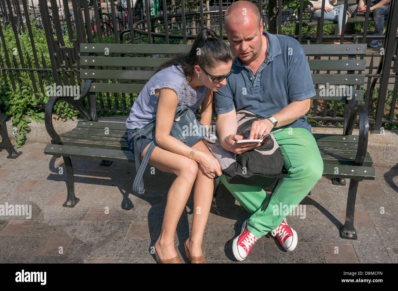 Tourist couple looking at a guide book dans un parc de poche dans la Petite Italie de New York City Photo Stock