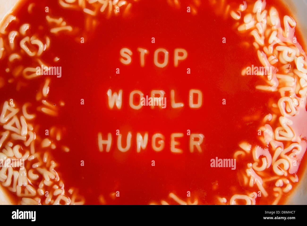 Soupe de tomate avec des lettres de nouilles message 'Stop' de la faim dans le monde Photo Stock