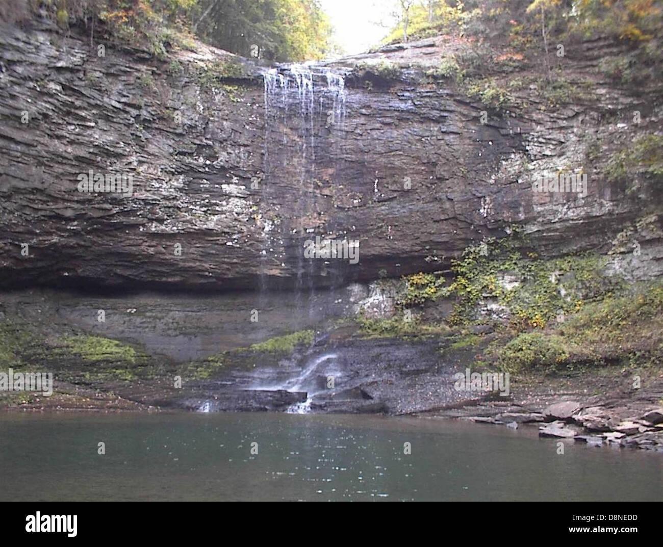 Plus de chute d'une falaise rocheuse dans un bassin d'eau. Photo Stock