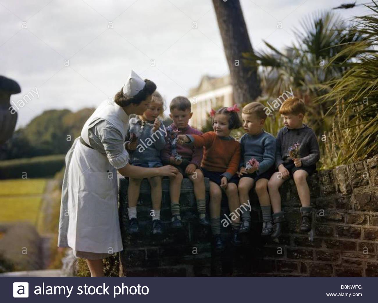 Une infirmière avec de jeunes personnes évacuées de Plymouth dans le jardin de la maison à Chaim Photo Stock