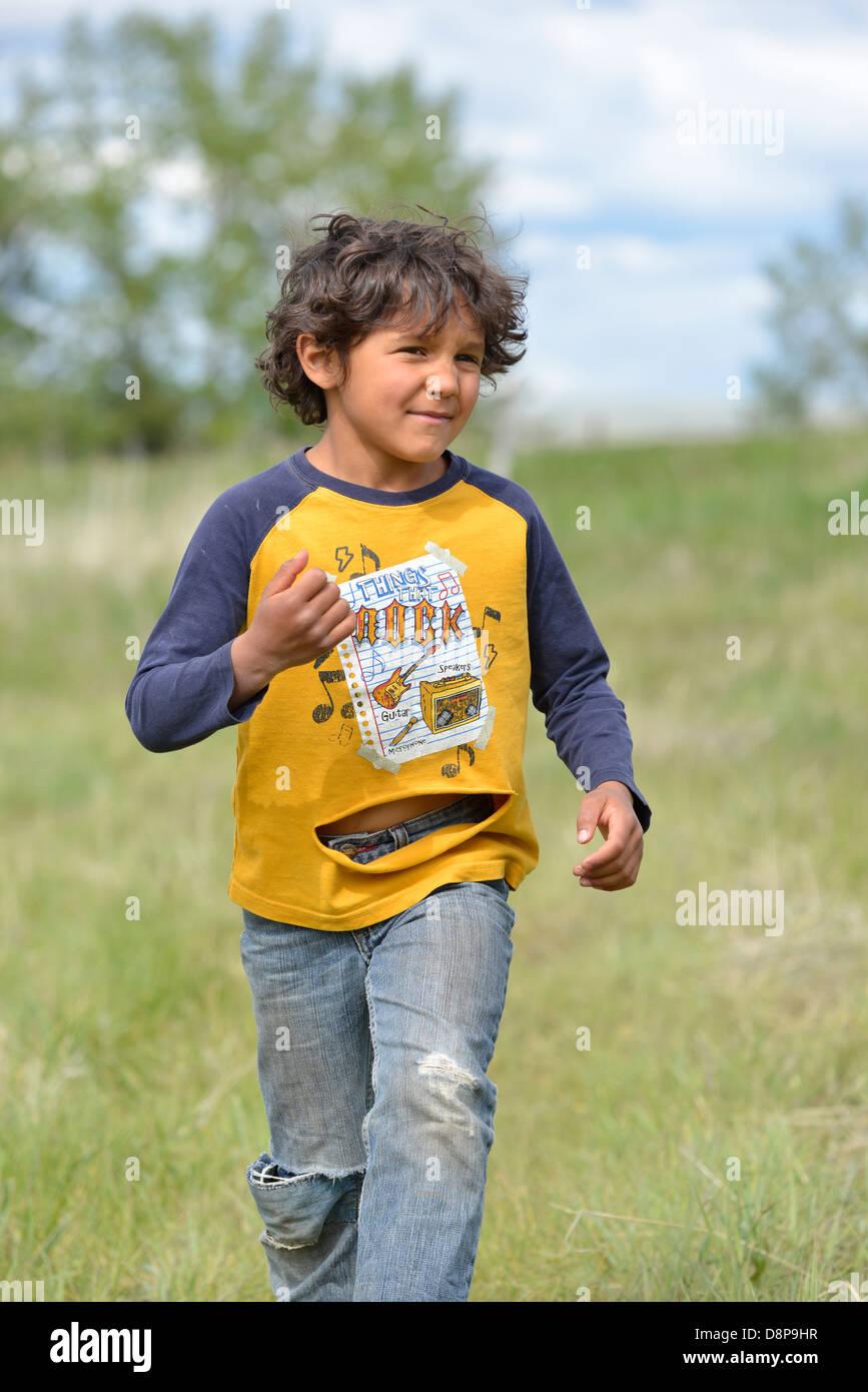 Jeune garçon courir avec une chemise déchirée, Wallowa Valley, Oregon. Banque D'Images