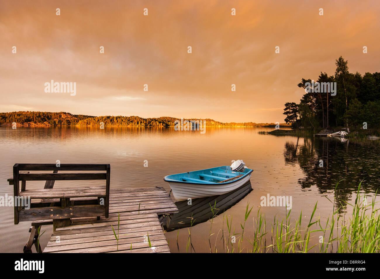 Petit bateau amarré à une jetée sur un lac en Suède, soir Photo Stock