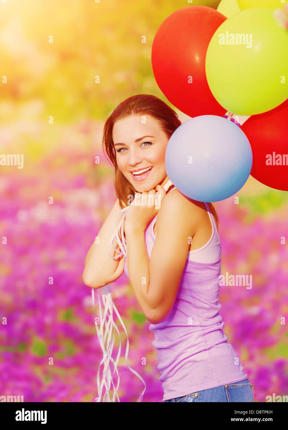 Jolie femme gaie s'amusant avec des tas de ballons colorés dans jardin de printemps, anniversaire, bonheur Photo Stock