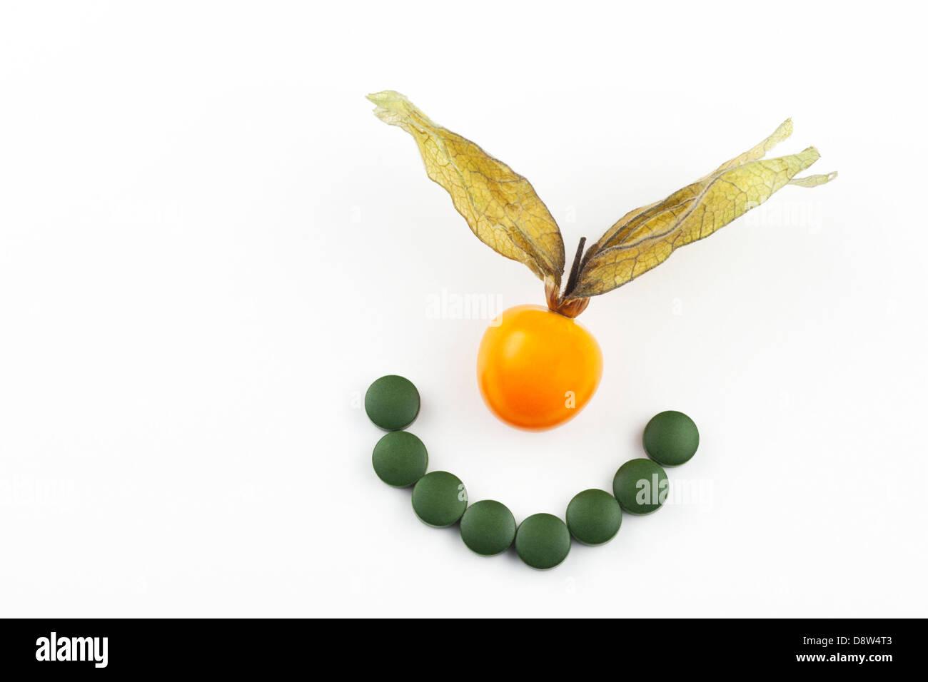 Chlorella comprimés dans un sourire et des golden berry Photo Stock