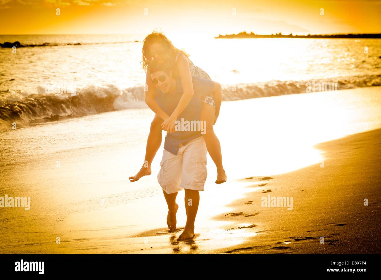 Jeune couple sur la plage à jouer sur le rivage il carry son style piggy back Photo Stock