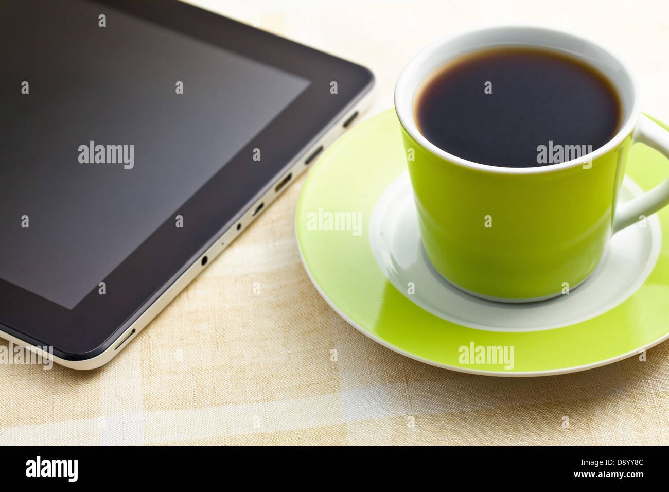 Café noir dans la tasse verte avec tablette ordinateur Photo Stock