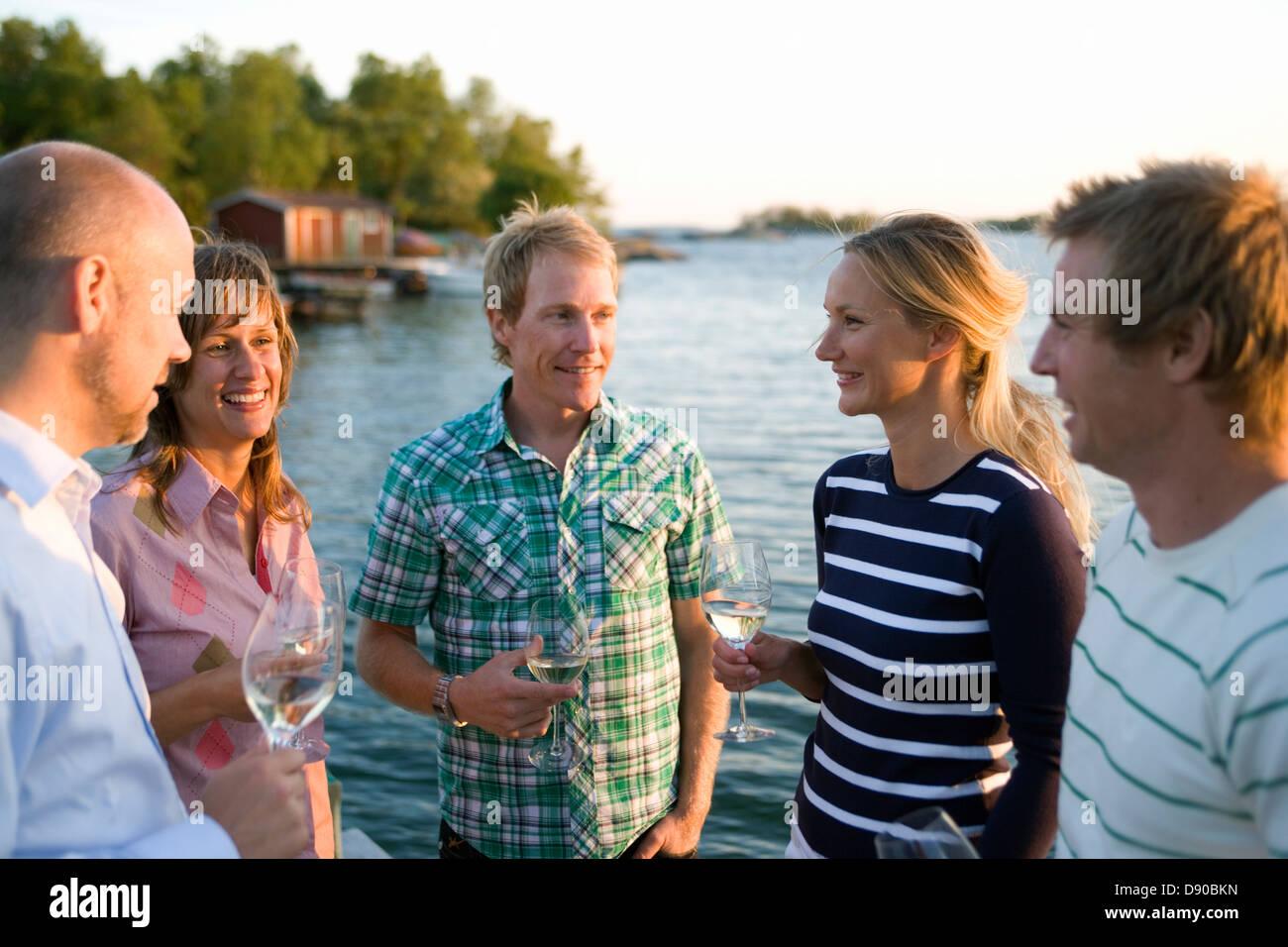 Cinq amis parler et boire, Fejan, archipel de Stockholm, Suède. Banque D'Images
