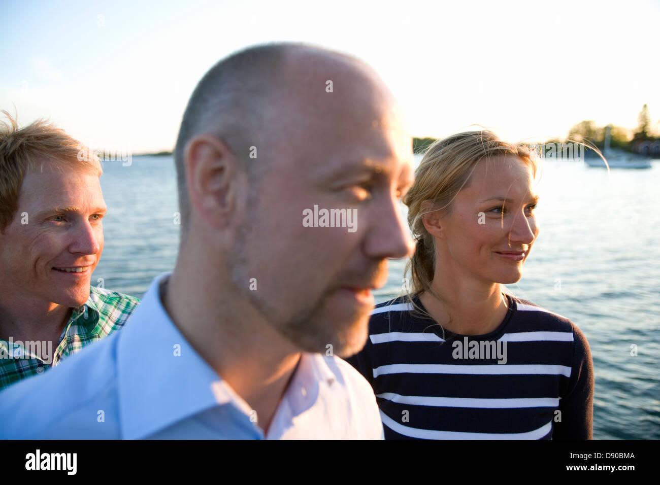 Trois personnes debout près de l'eau, Fejan, archipel de Stockholm, Suède. Banque D'Images