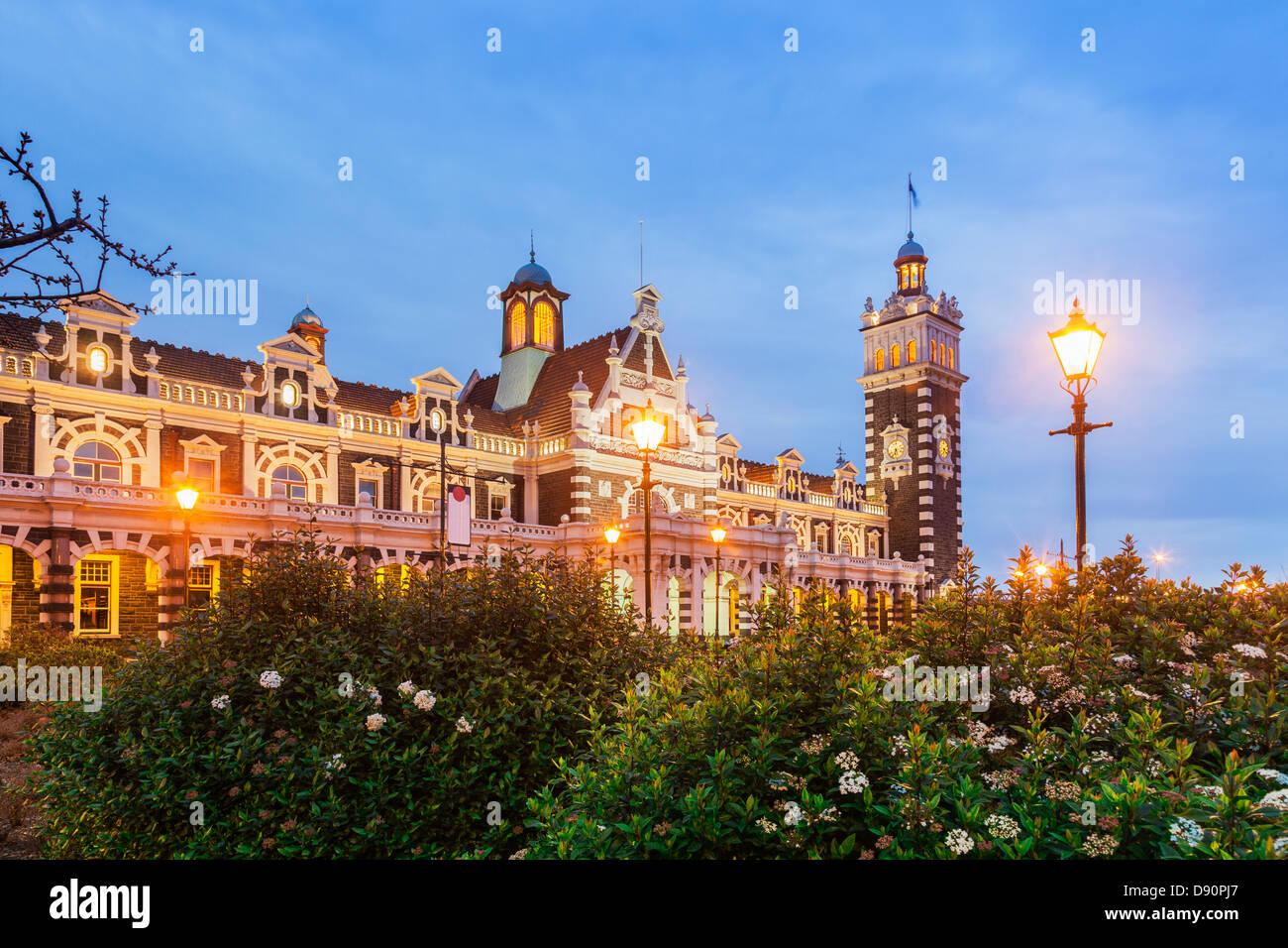La gare de Dunedin allumé au crépuscule. Banque D'Images