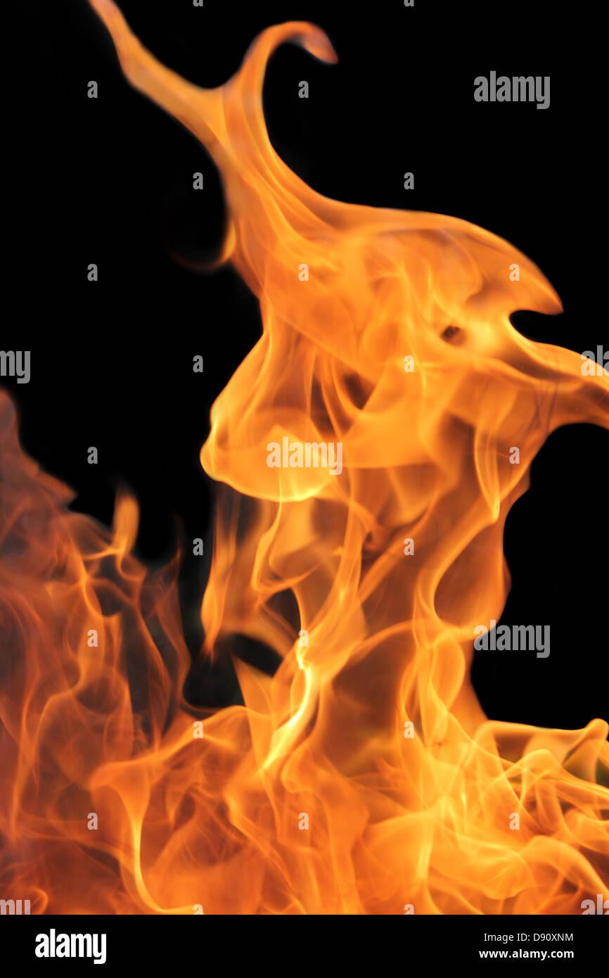 Des flammes orange lumineuses avec un fond sombre Photo Stock
