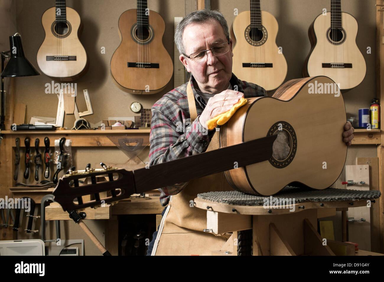 Luthier guitare acoustique finition en atelier Photo Stock