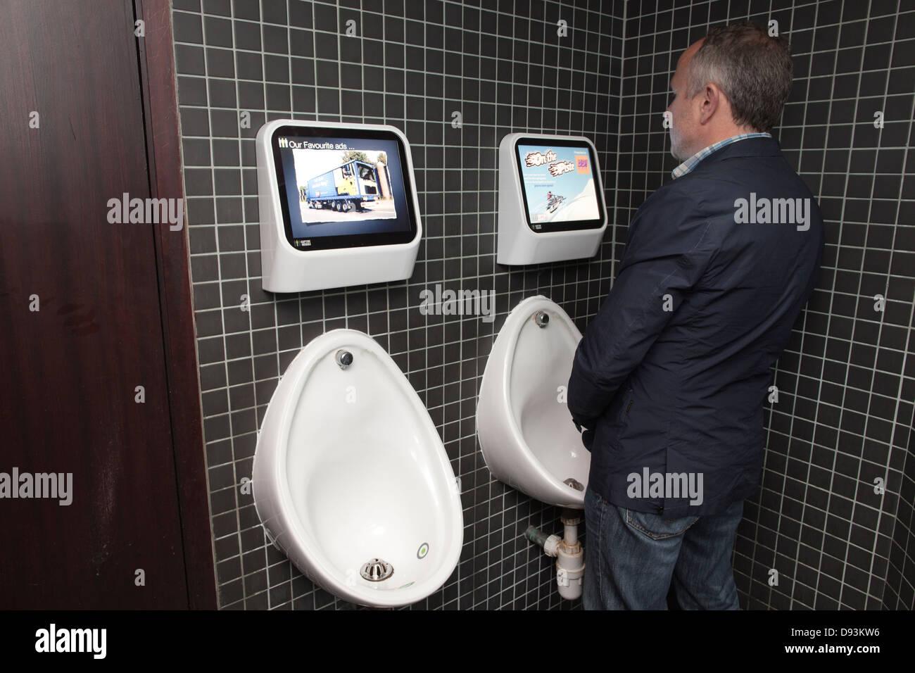 Des écrans de jeux vidéo au-dessus des urinoirs dans YO!Sushi, Pologne Street, London, England, Photo Stock
