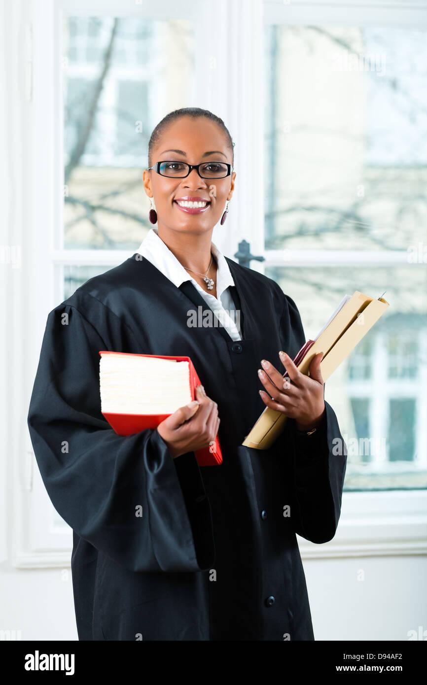 Jeune femme avocate travaillant dans son bureau avec un livre de droit et d'un fichier ou dossier Photo Stock