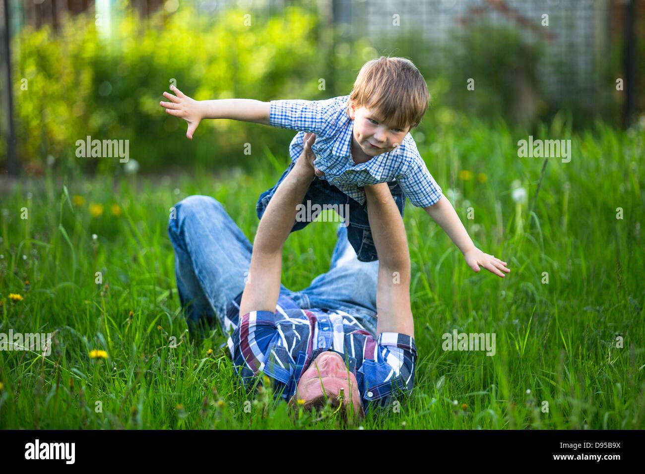 Père et fils jouant couché dans l'herbe dans le parc Banque D'Images