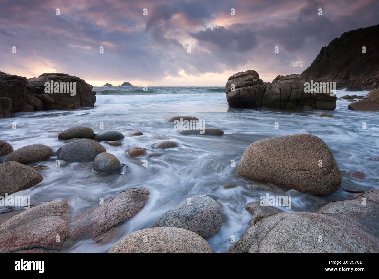 Coucher du soleil sur les rives rocheuses Porth Nanven, près de St Just, Cornwall, Angleterre. Photo Stock
