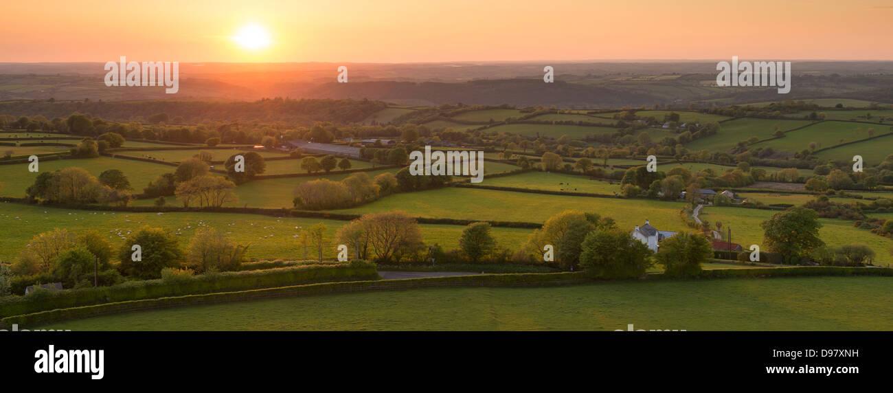 Coucher de soleil sur un paysage vallonné campagne du Devon, Devon, Angleterre. En été (juin) 2013 Photo Stock