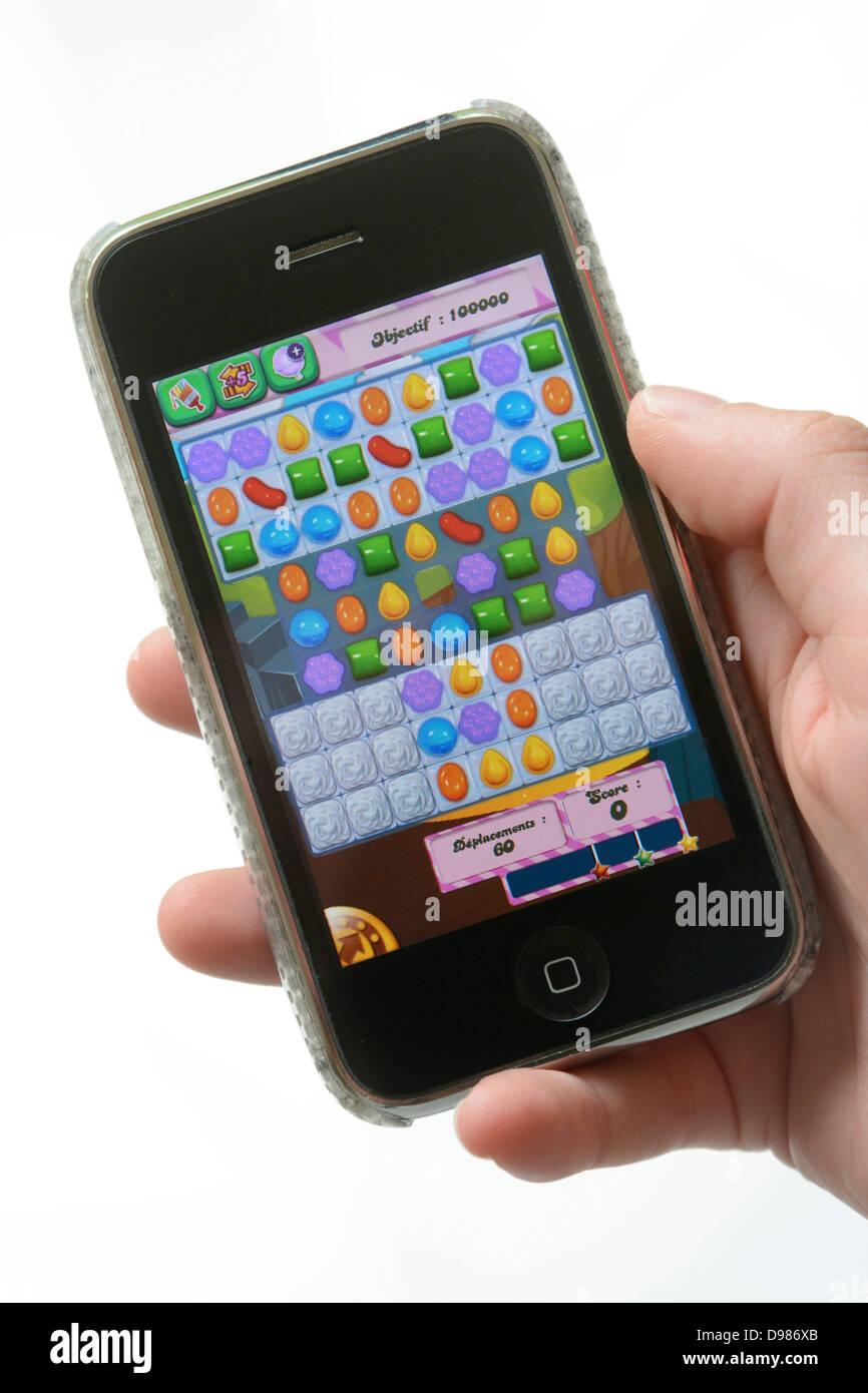 Jouer à un jeu sur un téléphone mobile Photo Stock