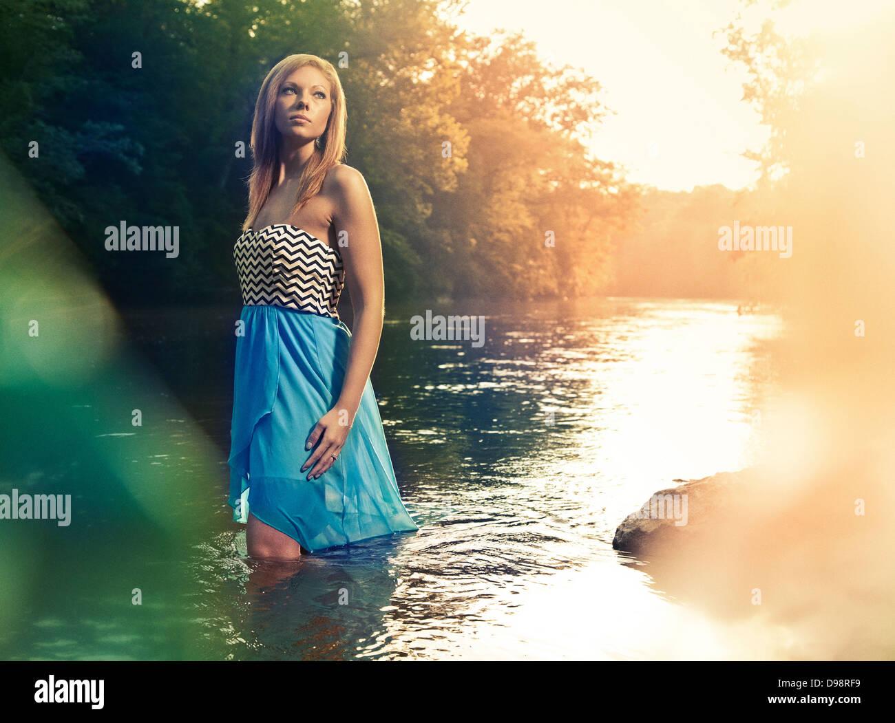 Femme en robe bleue walking in river pendant le coucher du soleil Photo Stock