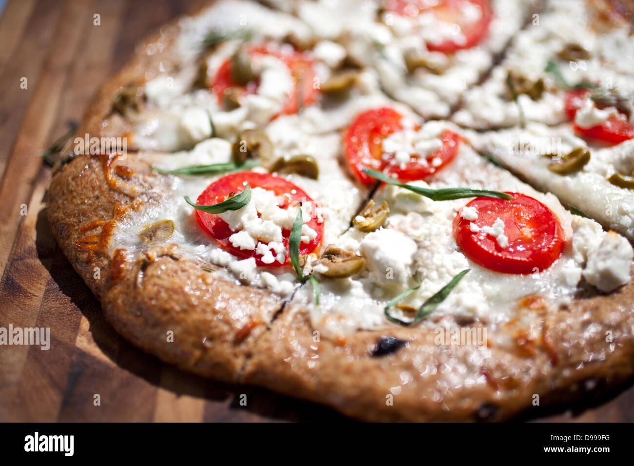Pizza au fromage blanc rustique avec des tomates en tranches sur une planche à découper Banque D'Images