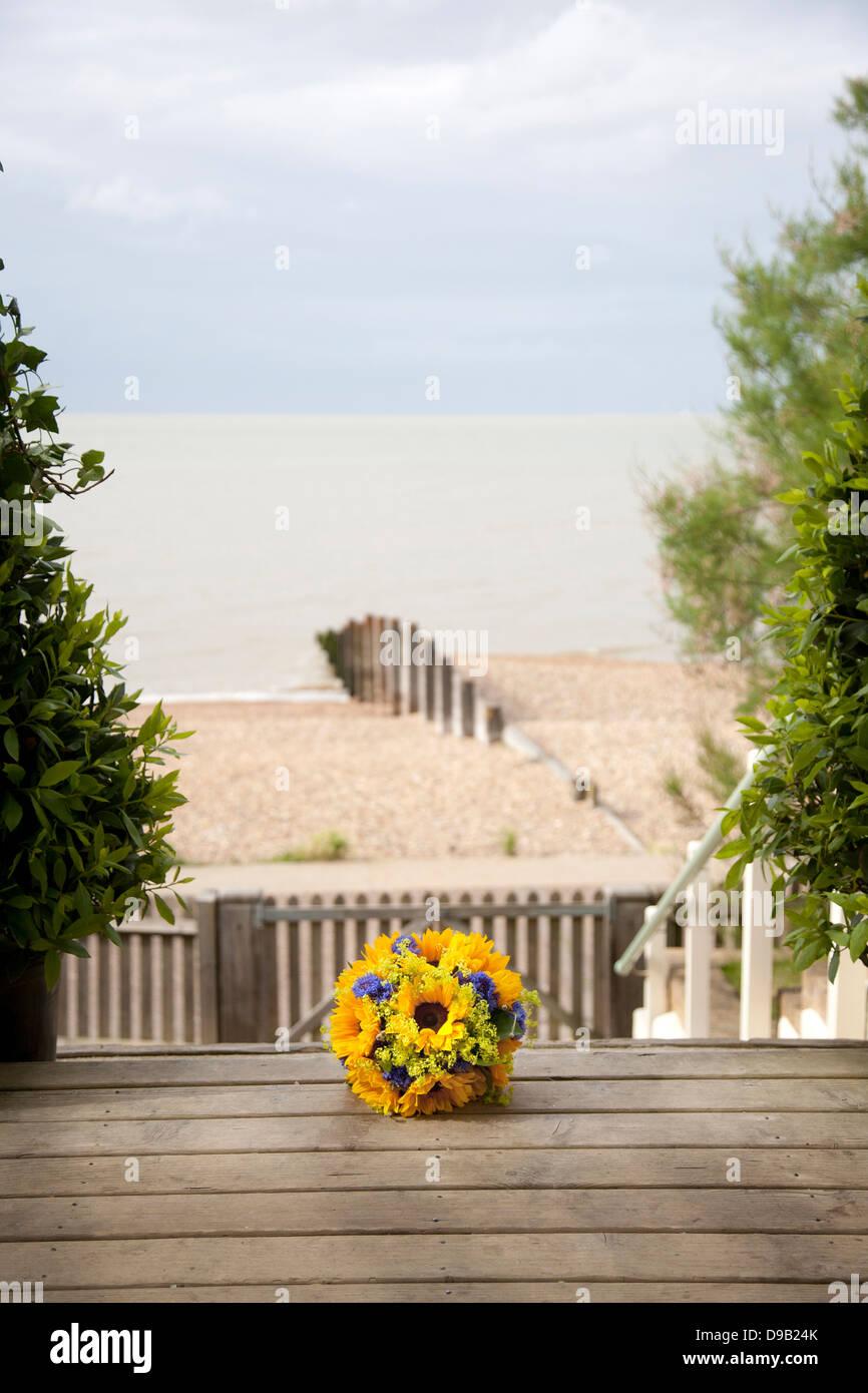 Bouquet de mariée avec des tournesols sur marches de bois de beach house salle de mariage avec vue sur plage et mer en arrière plan