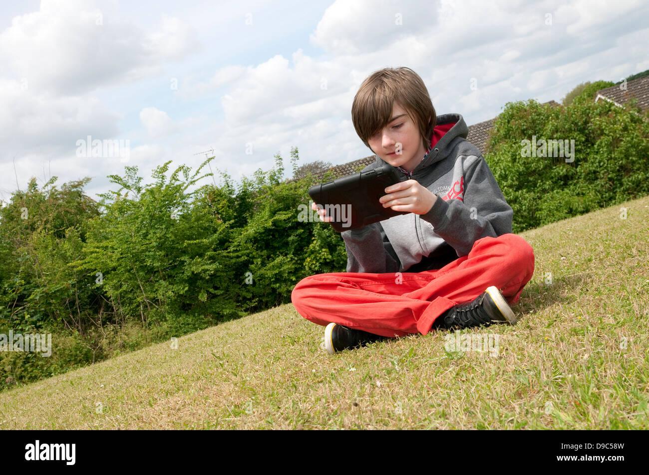 Jeune homme garçon à l'aide d'ipad mini tablet computer Photo Stock