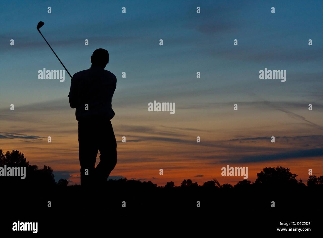 Silhouette d'un golfeur solitaire de l'achèvement d'une partie de golf au crépuscule Photo Stock
