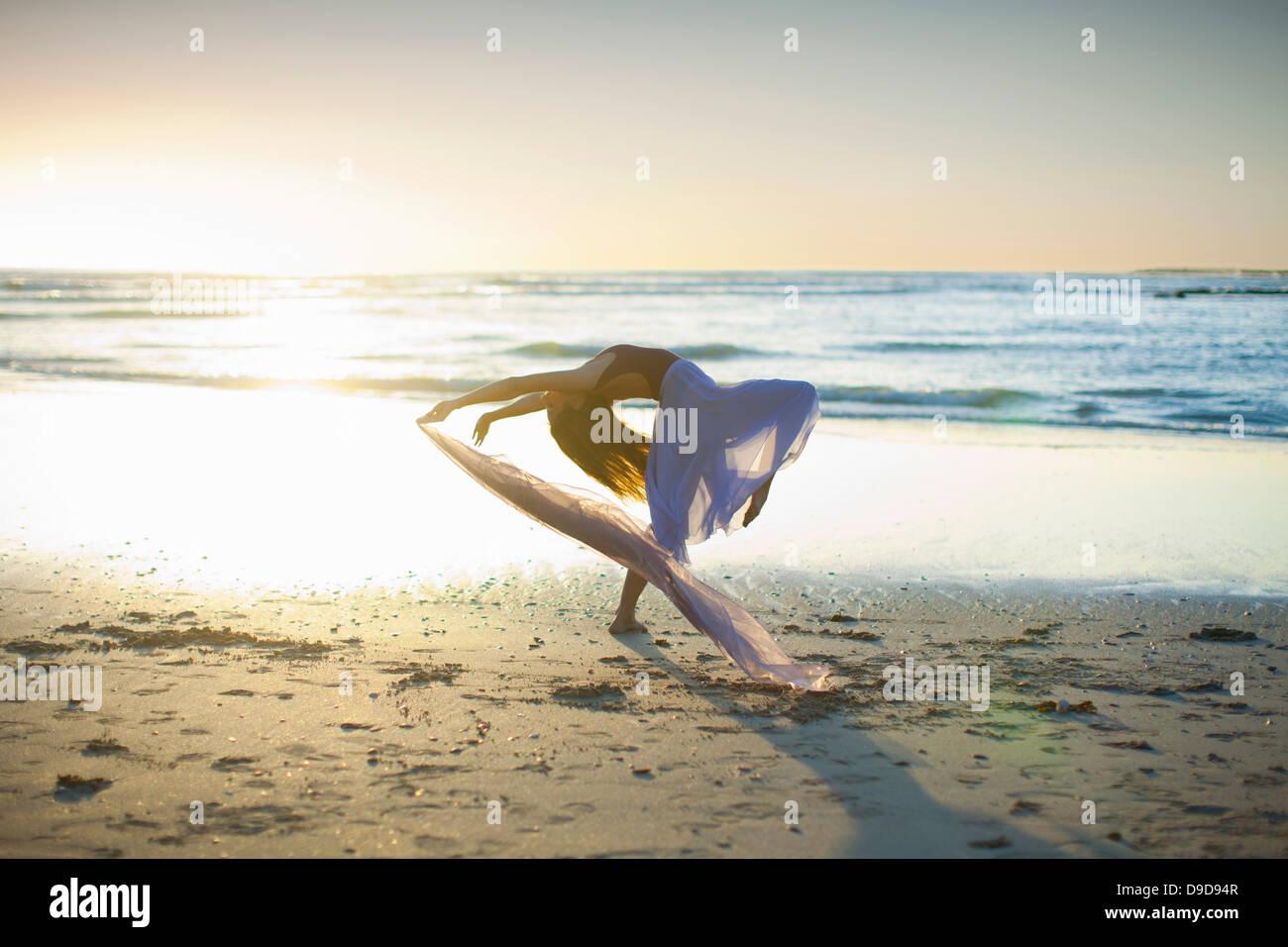 Jeune femme dansant sur la plage ensoleillée Photo Stock