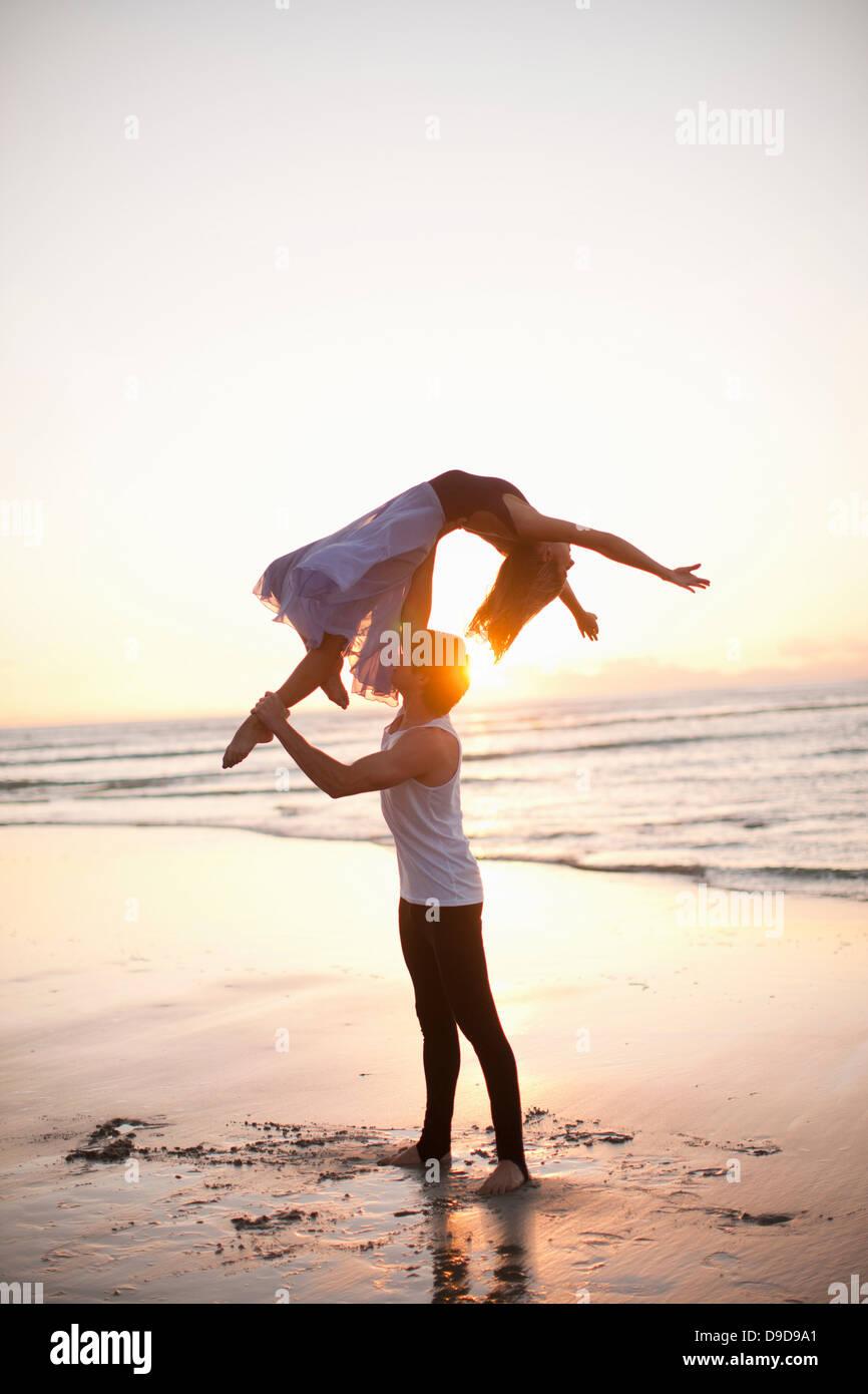 Jeune homme partenaire de danse de levage sur la plage ensoleillée Photo Stock