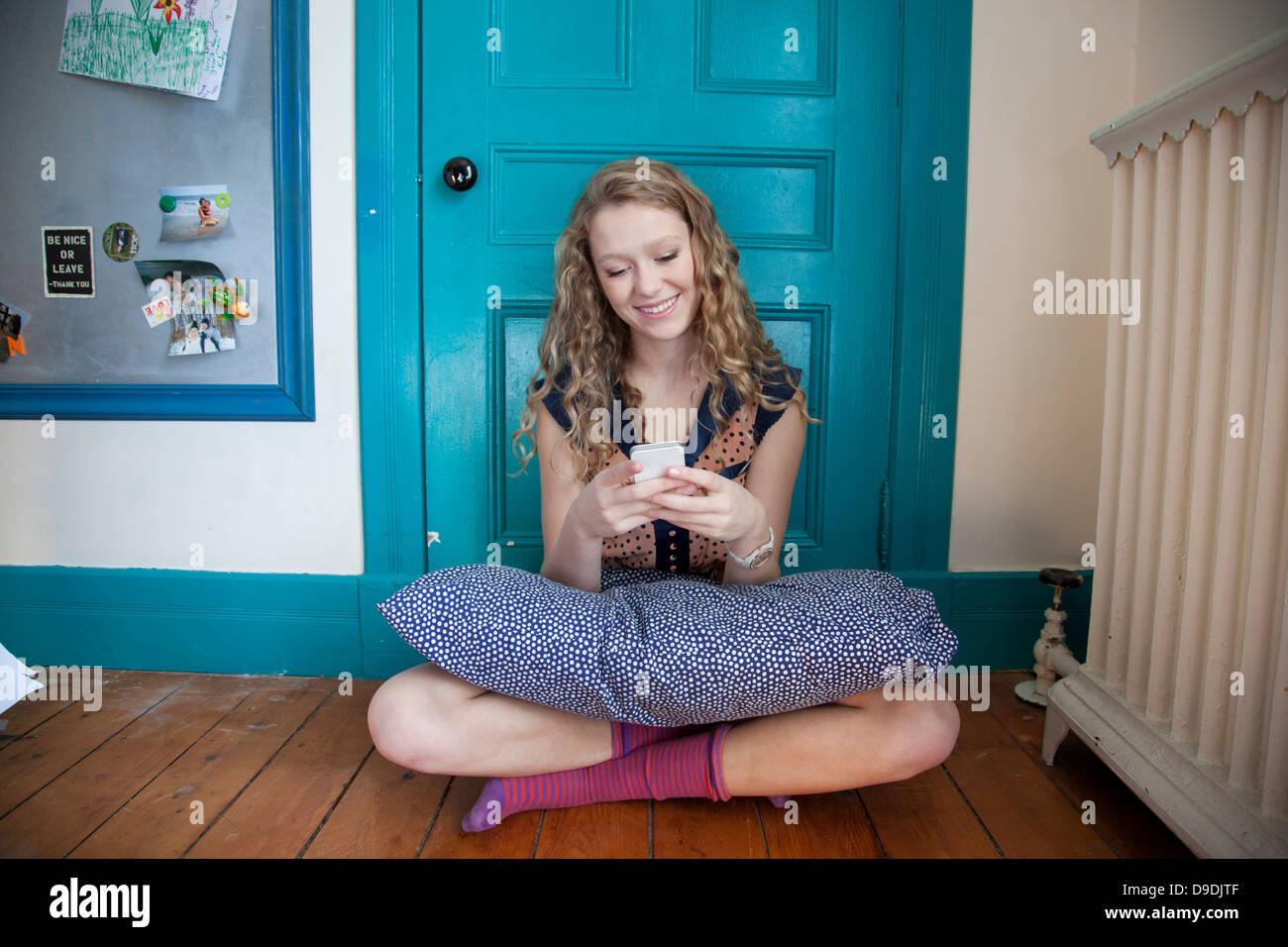 Adolescent assis devant la porte bleue, à l'aide de téléphone mobile Photo Stock