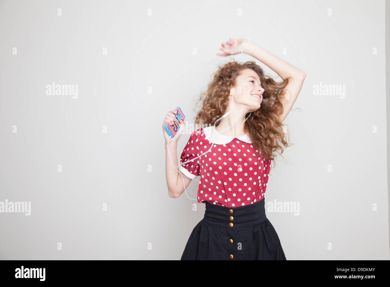 Girl wearing headphones, danse et holding mp3 player Photo Stock