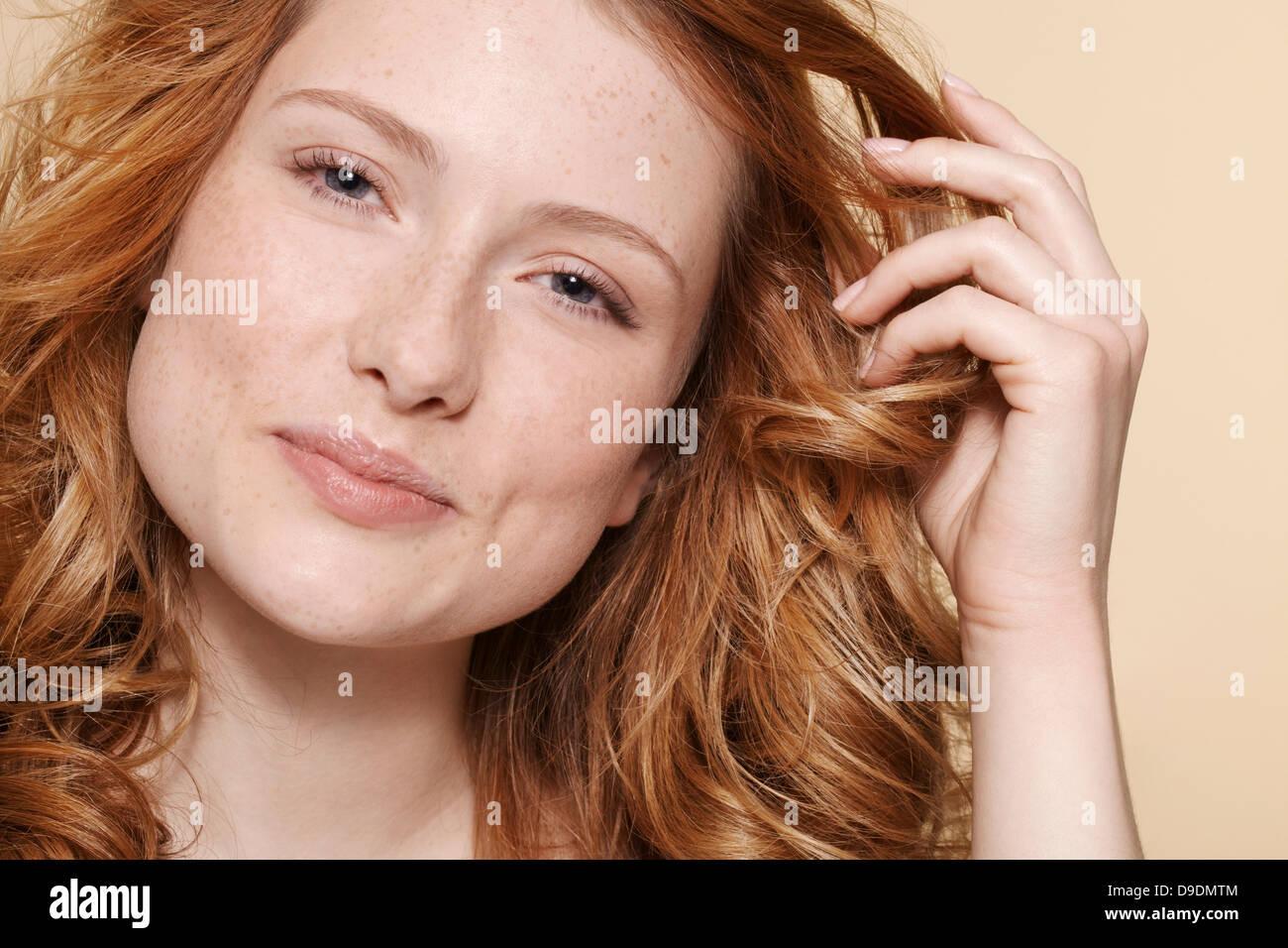 Studio shot of young woman with curly cheveux rouges, les cheveux dans la main Photo Stock