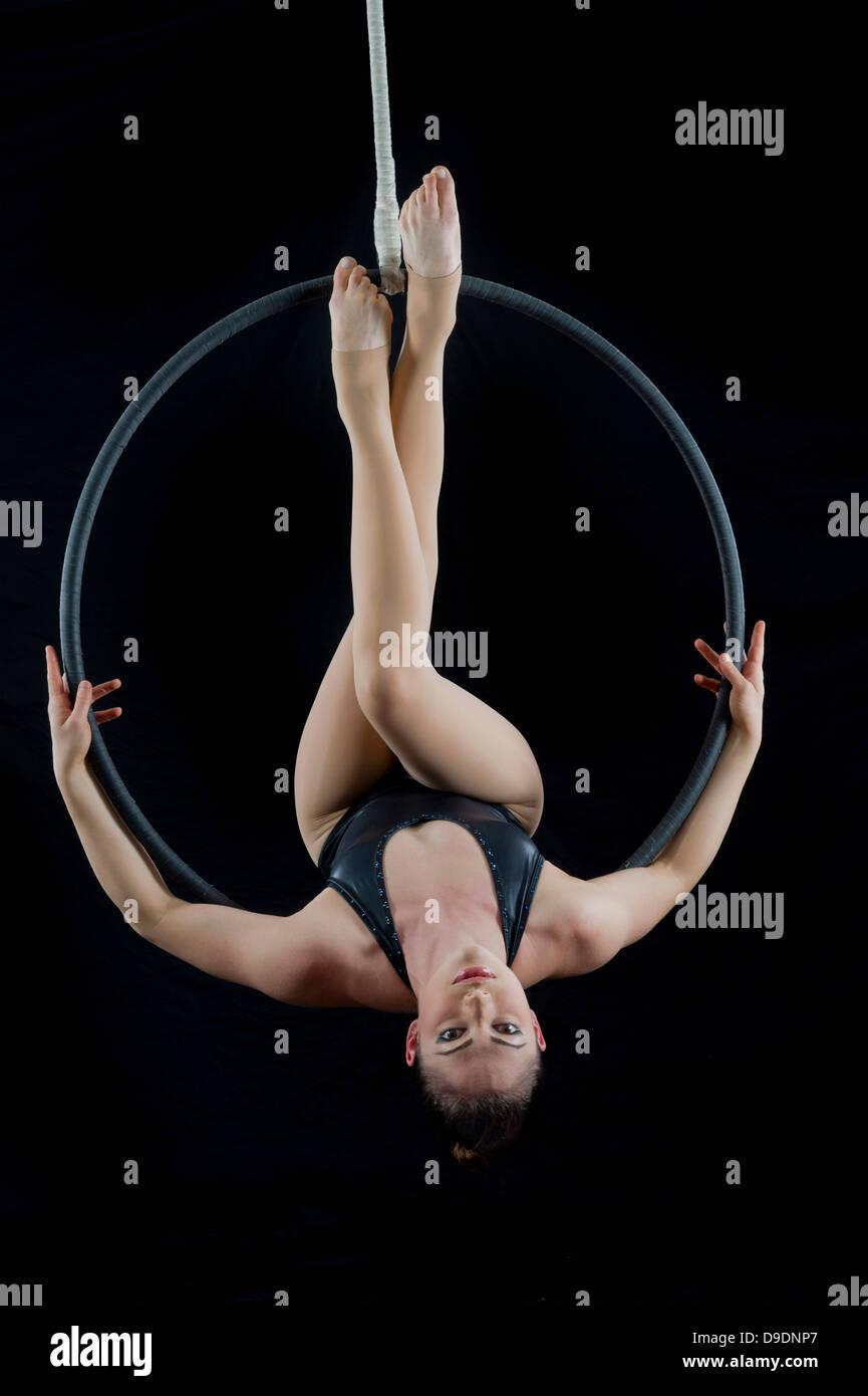 Aerialist performing on hoop en face de fond noir Photo Stock