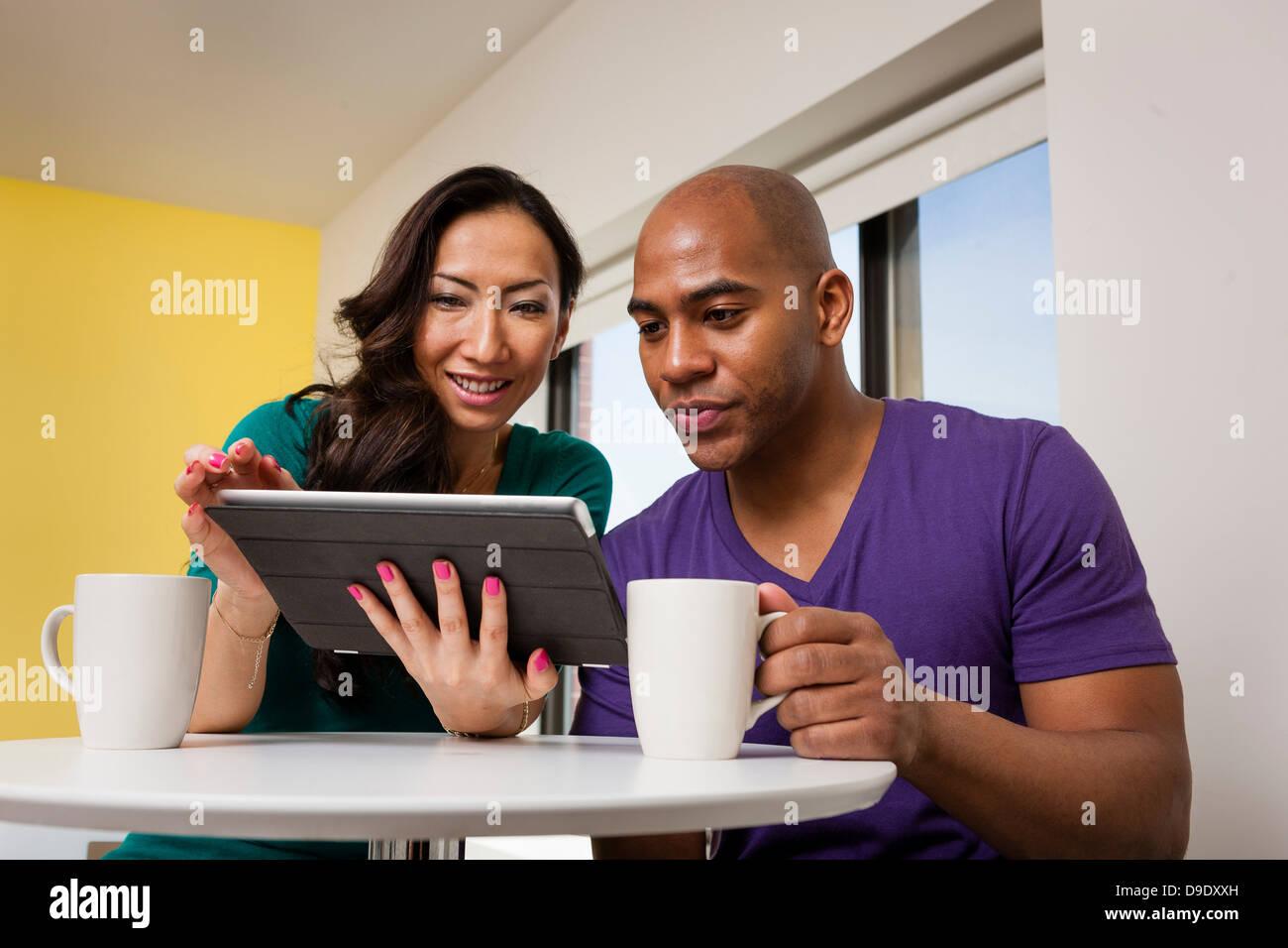Couple looking at digital tablet et boire du café Photo Stock