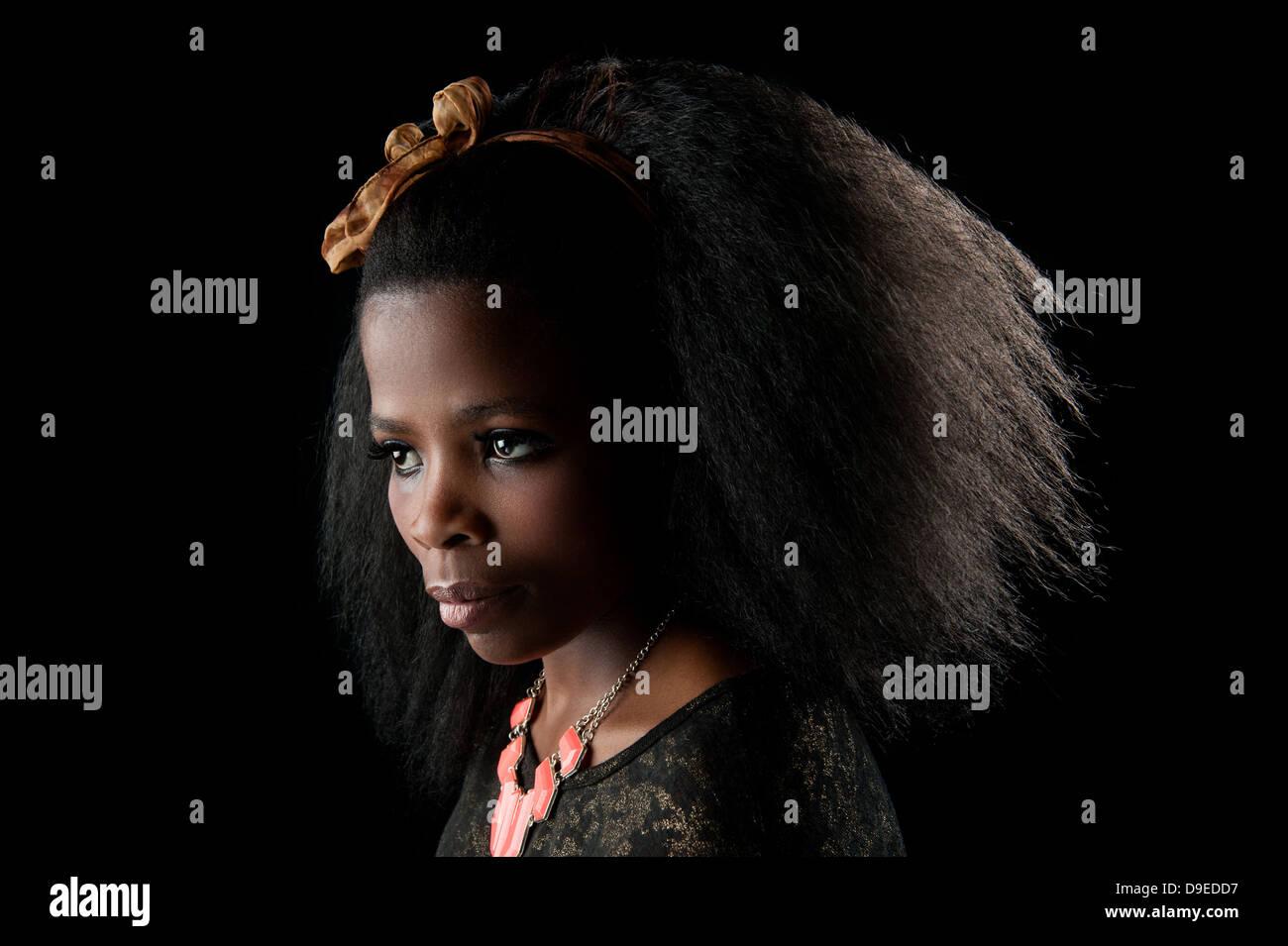 Jeune femme africaine avec de beaux cheveux afro, une clé faible background studio shot. L'expression faciale Photo Stock