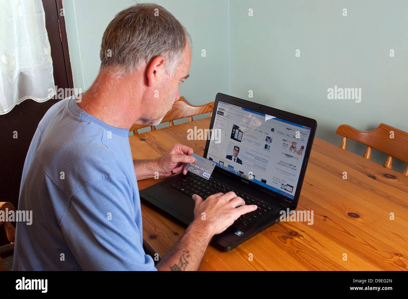 Un homme d'âge moyen à la maison en ligne Photo Stock