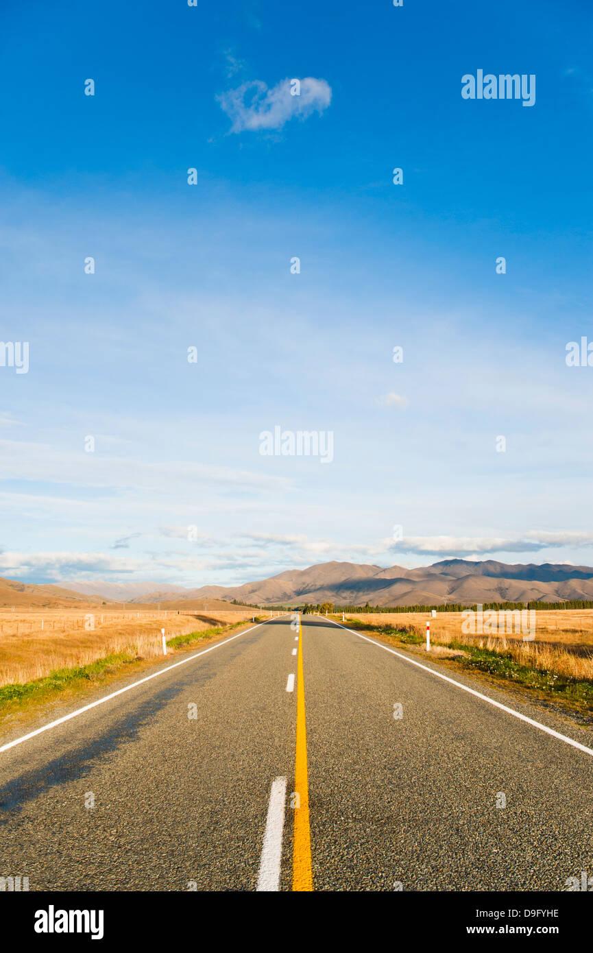 Longue route en ligne droite dans l'Otago, île du Sud, Nouvelle-Zélande Photo Stock