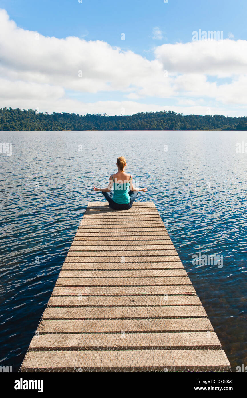 Femme méditant sur une jetée, lac Ianthe, West Coast, South Island, New Zealand Photo Stock