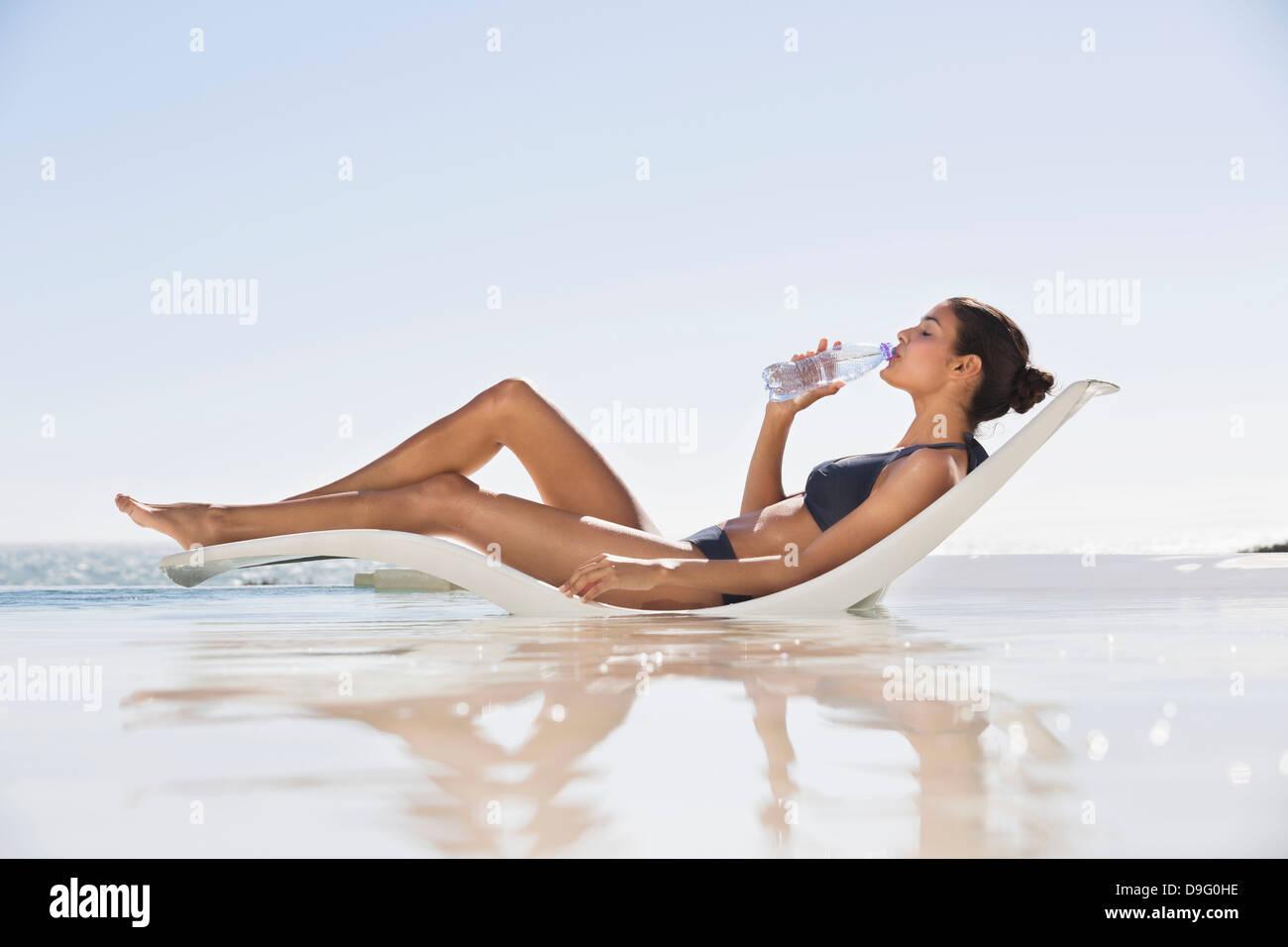 Belle femme l'eau potable sur la plage Banque D'Images