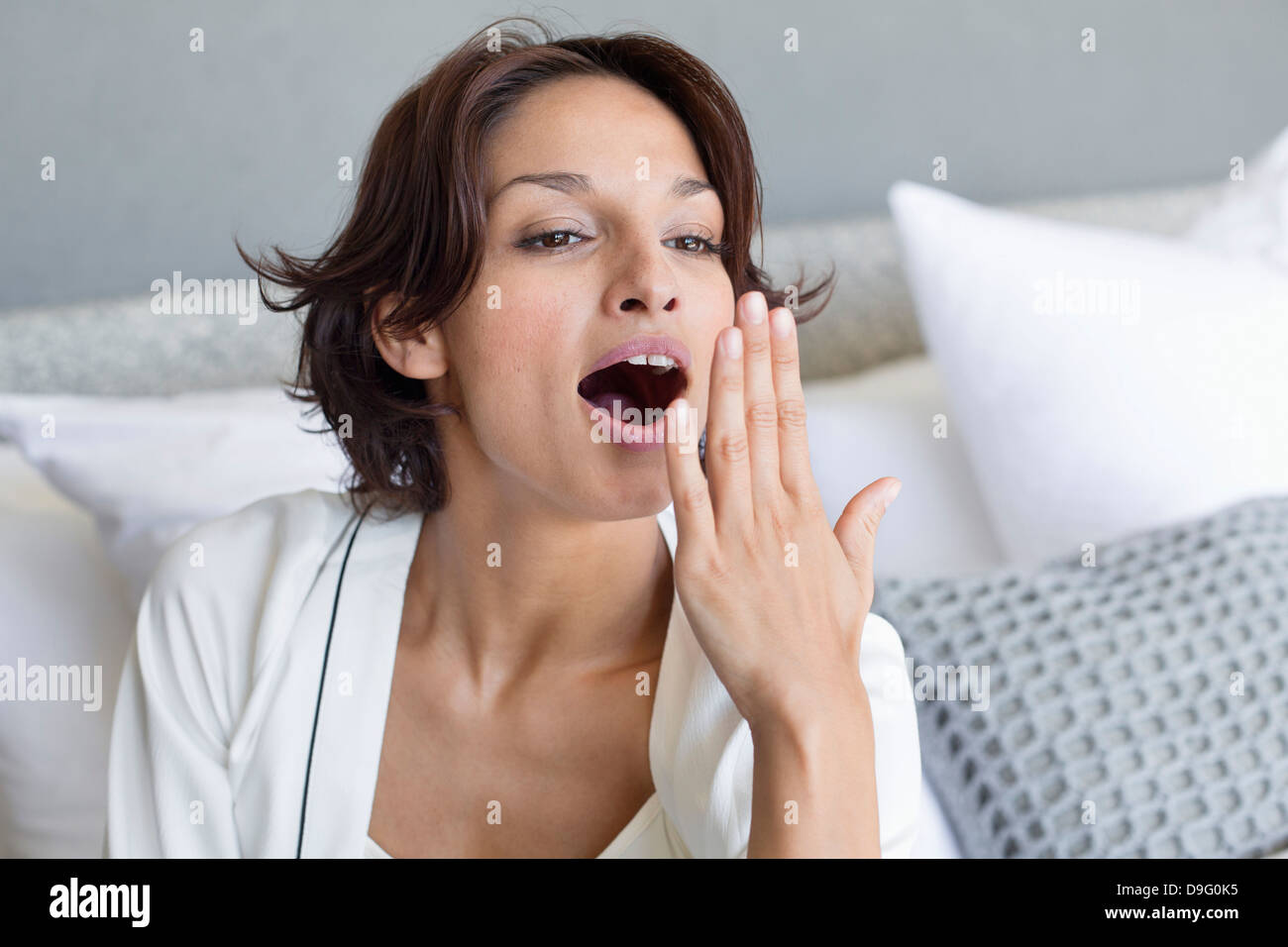 Woman yawning sur le lit Photo Stock