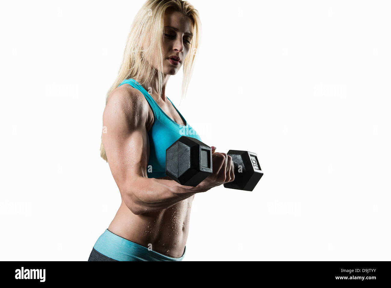 Jeune femme effectuant des biceps, studio shot Photo Stock