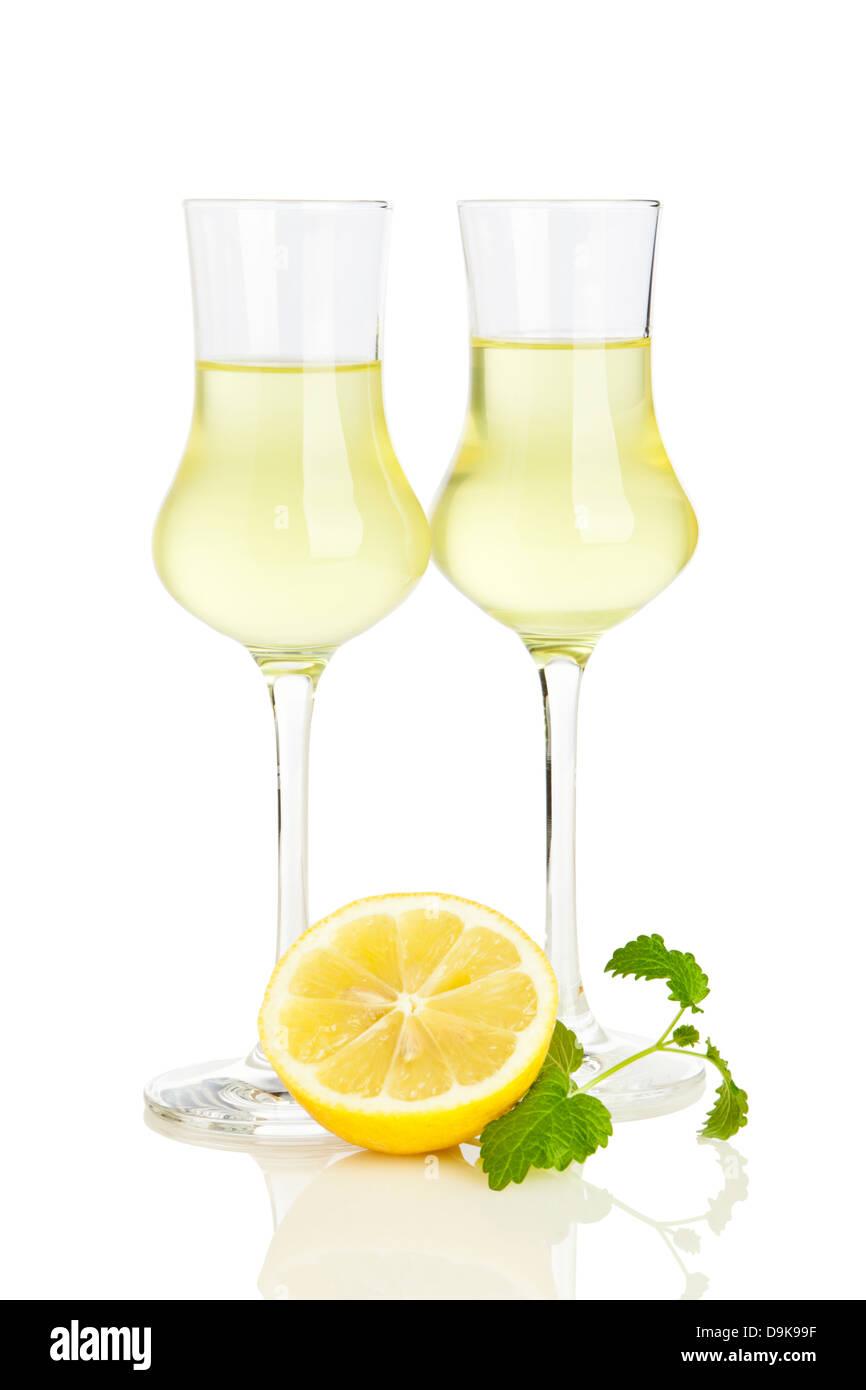 Deux verres de liqueur Limoncello italien, moitié de citron et feuilles de mélisse isolé sur fond blanc Banque D'Images