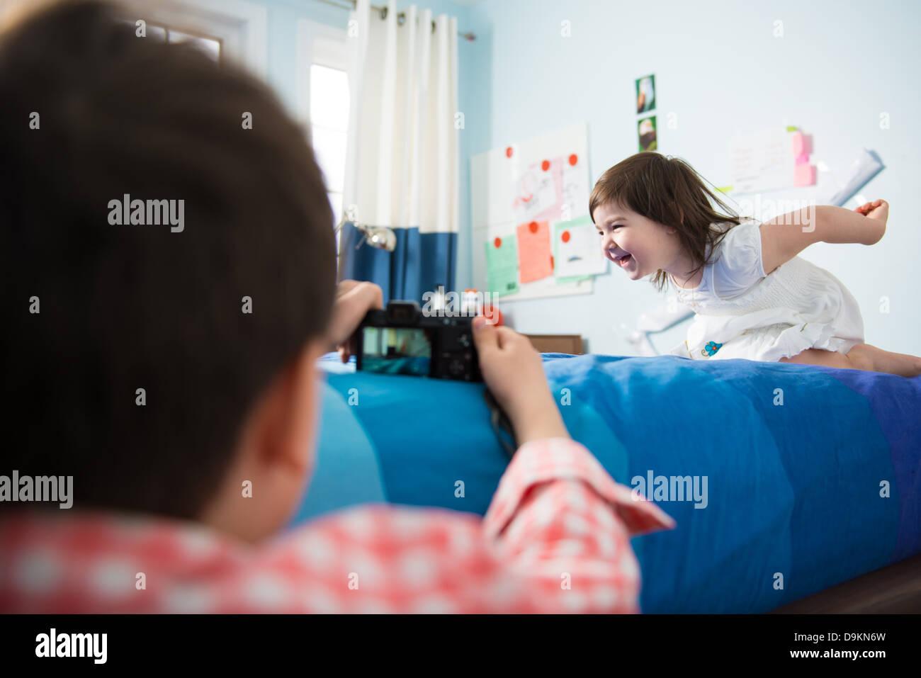 Garçon prendre des photos de sœur jouer agissant Photo Stock