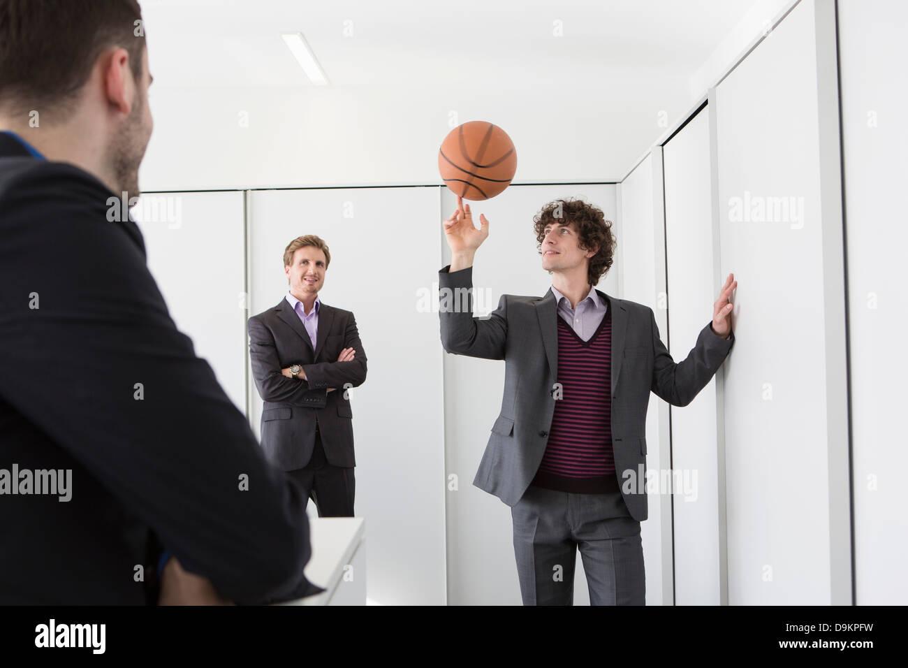 Office worker spinning basketball on finger Photo Stock
