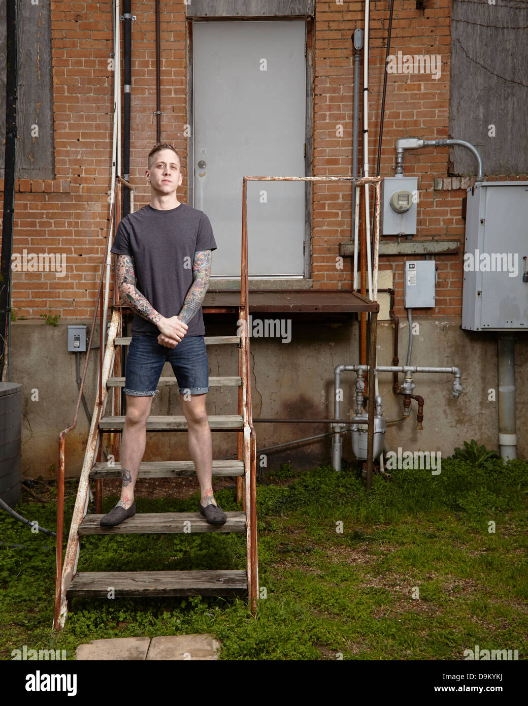 Portrait of young tattooed man standing on staircase Photo Stock