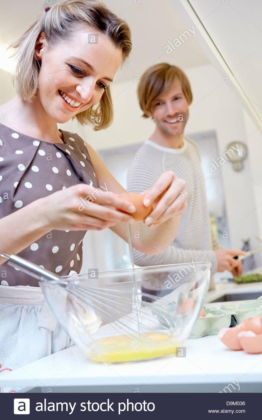 Fissuration femme oeufs dans le bol Photo Stock