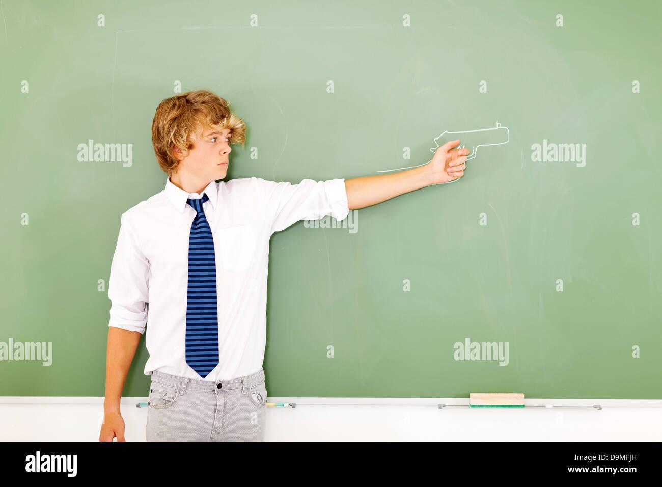 Lycéen violent tenant un pistolet tiré on chalkboard Photo Stock