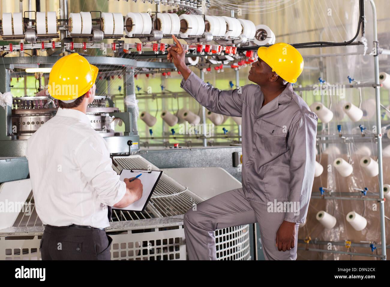 Gestionnaire d'usine de textile et le tissage de fils de contrôle ouvrier sur machine Banque D'Images