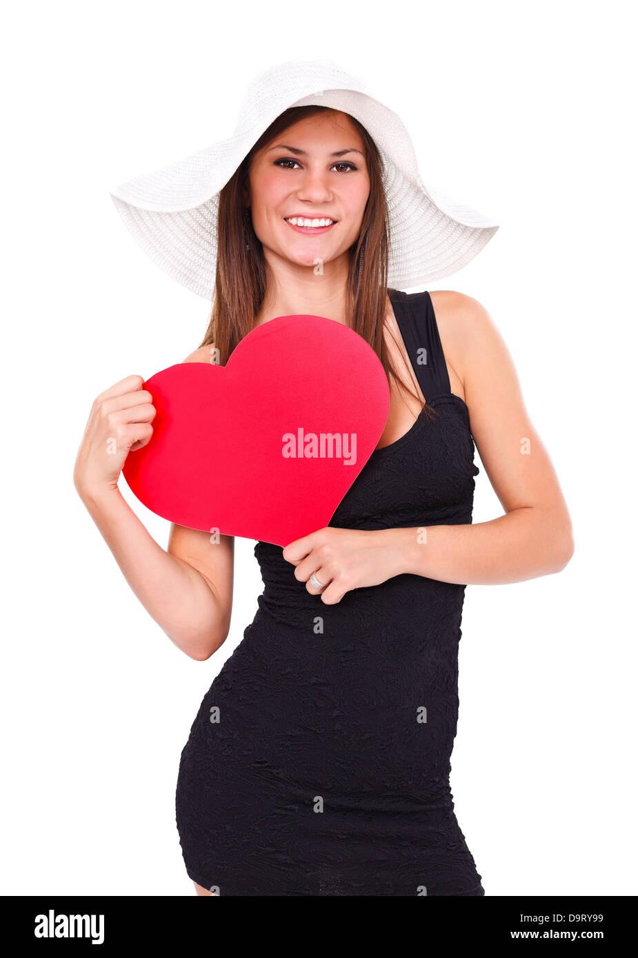 d110ac57cd931 Jeune femme en robe noire et blanc summer hat holding un cœur rouge posing  in studio